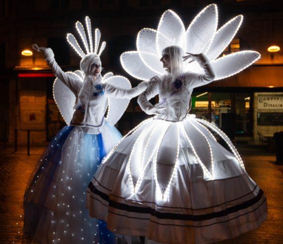 Échasses éclairées, échasses à led, marcheurs sur échasses, divertissement à LED, acte éclairé, acte de Noël, événement de Noël, spectacle d'hiver, sur le thème des fleurs, échasses de fleurs, fête blanche, événement à thème blanc, échasses blanches